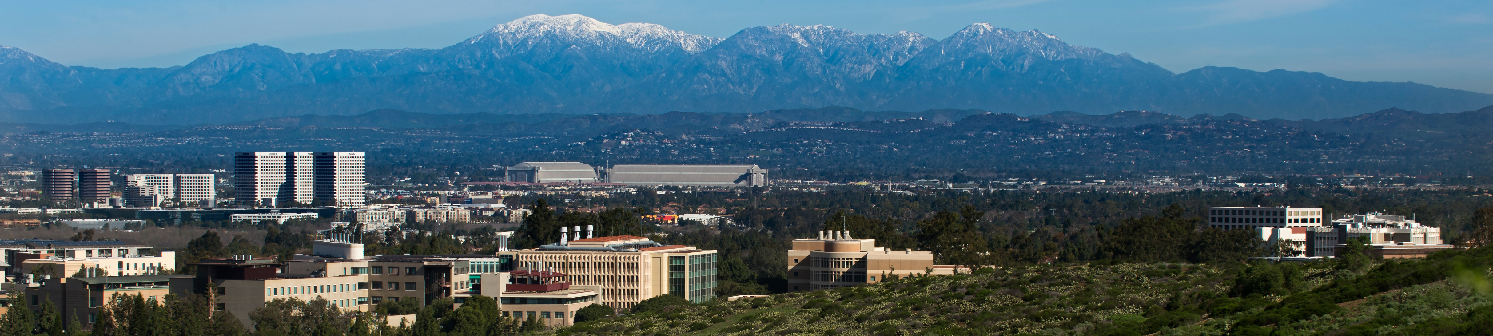 View of portion of campus and Irvine with snowcapped mountains in the background