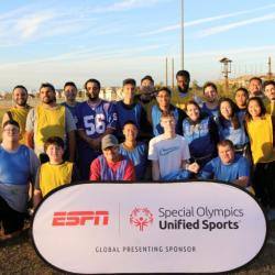 Group of participants on ARC fields behind sign Special Olympics Unified Sports