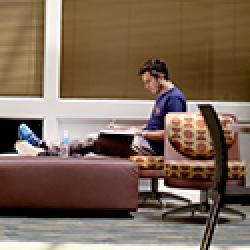 Student sits in study area writing in a notebook